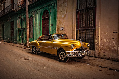 Classic yellow car (taxi) from the 1950's parked on residential street in Old Havana