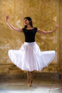 Cuban National ballerina standing en pointe  with both arms outstretched and skirt swirling in old Havana Mansion, Cuba