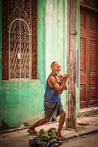 Cuba, Havana.  An old man shows us his boxing prowess along a residential street in Old Havana.