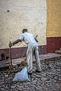 Cuba, Trinidad.  A street sweeper busy at work on a cobblestone street in historic Trinidad, UNESCO, World Heritage Site