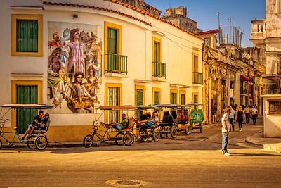 Cuba, Havana. a group of pedicabs wait under a street mural on a busy corner in Havana.
