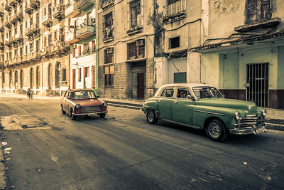 Cuba, Havana. Classic old cars being driven on street in downtown  Havana.