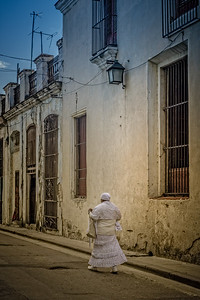 Cuba, Havana. A Priestess of Santeria wearing all white is waling along the street.