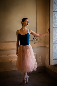 Cuban National ballerina standing en pointe at window of old Havana Mansion, Cuba