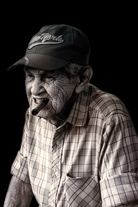 Cuba, Havana.  Portrait of an old man wearing a New York cap with a cigar in his mouth.