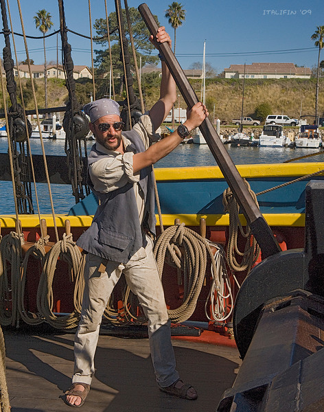 A crew member, dressed in period costume, raises the anchor prior to taking locals on a cruise.