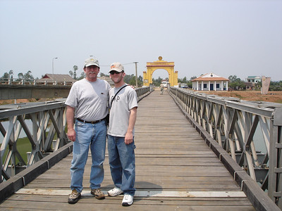 Your tour guide Gene Miller and his son Eric standing on the Peace Bridge which spans the Song Ben Hai (River) which use to separate North and South Vietnam.  -  Tour #VN05031