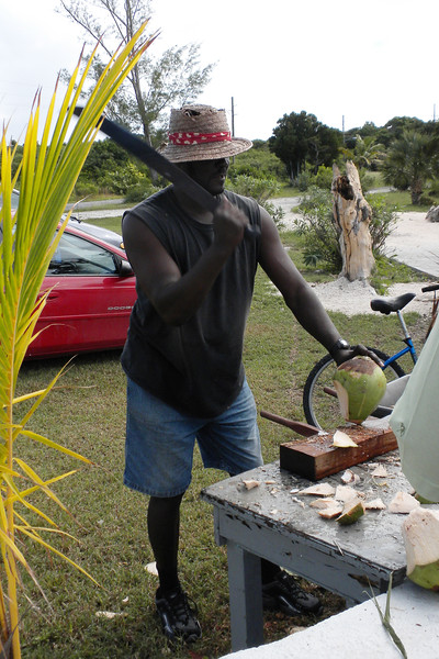 Machete wielding man, cutting open coconuts for the milk - $5.00 per coconut