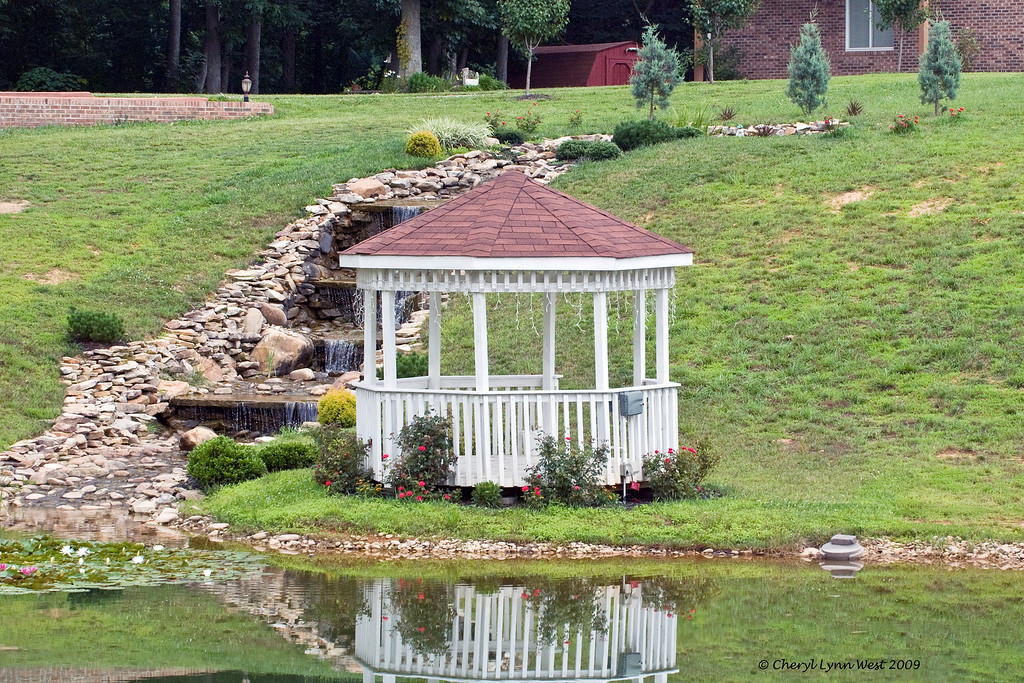 Gazebo and waterfall in the front yard of a country home.