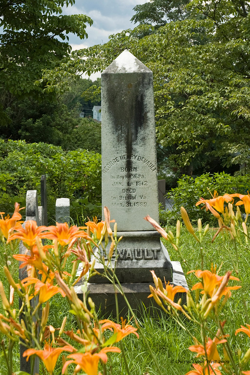 Center marker for family plot, surrounded by flowers.
