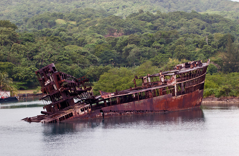 Wrecked and rusted hull of a ship in the port of Roatan