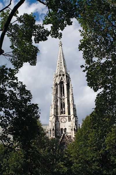 Votiv church spire framed by trees, Vienna, Austria, Europe.