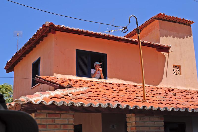 Brazilian villager looking out of his window, Canoa Quebrada, Ceara, Brazil, South America.