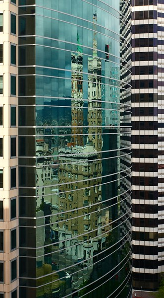 Reflection of an older buiding in a modern glass wall, Oakland, California, USA.