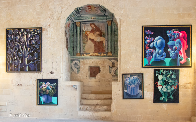 Ercole Pignatellli's art exhibit in the Castello Carlo V, seems quite in contrast to the old Byzantine style mural on the wall.