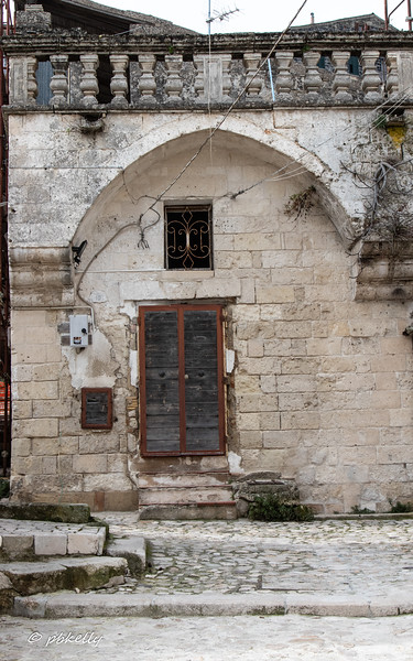 An  old door in Matera with obvious attempts to modernize - wires, and the grey box  which talks about night light.
