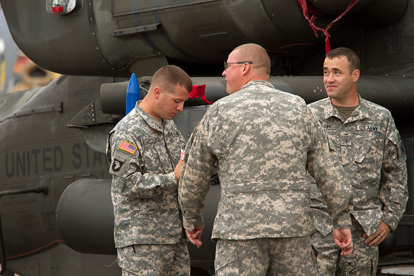 US Military personnel huddle next to an AH-64 Apache Gunship<br /> 2011 Cleveland National Air Show