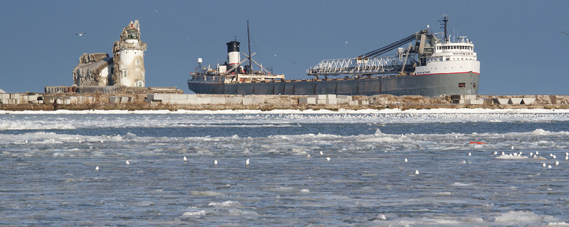 """The Manistee sails past the Cleveland Harbor West Pierhead Lighthouse on a pleasant December day.<br /> Sized for both 20x8"""" and 30x10"""" Panoramic Portrait."""
