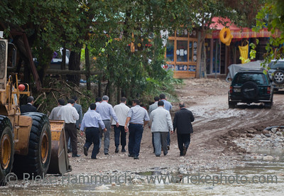 Men leaving Shovel of a Bulldozer - Earth Mover used  as a Ferry after Flood Disaster in Olympos, Turkey, Asia