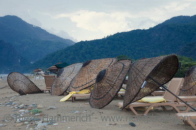 Damaged Umbrellas on Beach in front of Taurus Mountains - Cirali, Turkey, Asia