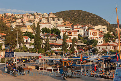 Kas, Turkey - October 15, 2009: Picturesque Harbor of the village Kas in Turkey. Boat and diving tours for tourists starts here. After work people are relaxing at sunset. Kas is a small fishing, diving, yachting and tourist town on the Turkish Riviera and part of Antalya Province.
