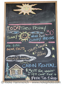Black board with handwritten weather forecast and offering cabin rentals - Campground in British Columbia, Canada