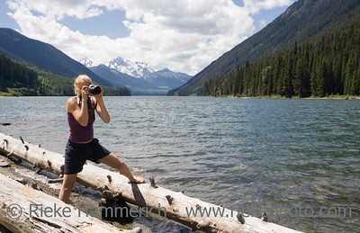 Young Woman with Camera on Floating Logs – Duffey Lake, Coast Mountains, British Columbia, Canada
