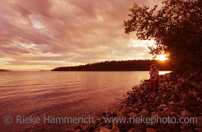 Young woman on lakeshore enjoying sunset - Green Lake, South Cariboo, British Columbia, Canada