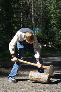 teen with an axe - chopping wood on a campground in canada - adobe RGB