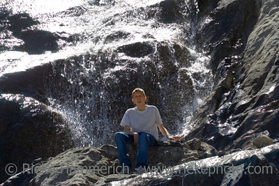 teenager sitting in front of bow glacier falls - banff national park, canada - adobe RGB