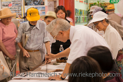 Vancouver, British Columbia, Canada – August 6, 2005: Mature artist painting Chinese calligraphy surrounded by an interested audience in Chinatown of Vancouver, Canada. Chinatown in Vancouver is one of the largest historic Chinatowns in North America and a popular tourist attraction.