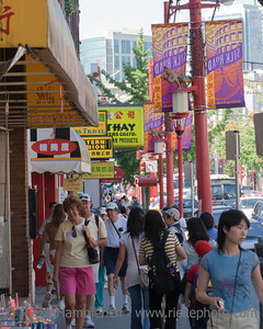 Vancouver, British Columbia, Canada – August 6, 2005: Street Scene with Pedestrians and Stores in Pender Street in Chinatown of Vancouver, Canada. Chinatown in Vancouver is one of the largest historic Chinatowns in North America and a popular tourist attraction.