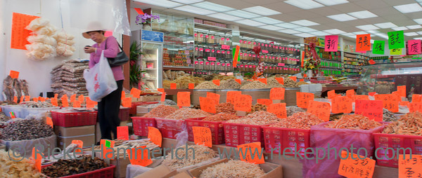 Vancouver, British Columbia, Canada – August 6, 2005: Chinese Customer leaving Traditional Chinese Medicine Store (TCM) in Chinatown of Vancouver, Canada. Ingredients include dried fish, shrimps, shellfish and cuttlefish. Chinatown in Vancouver is one of the largest historic Chinatowns in North America and a popular tourist attraction.