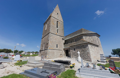 La Pernelle, France - July 01, 2011: Medieval church Sainte Pétronille with cemetery in La Pernelle, France. The Sainte Pétronille church was built in traditional norman style with granite stones and with slate shingles on the roof.