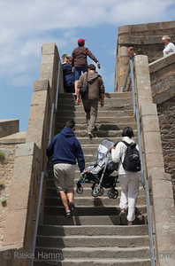 SAINT-MALO, FRANCE - JULY 6: People climbing steps in old town of Saint-Malo, France on July 6, 2011. Parents are carrying a chicco baby stroller with their child upstairs.