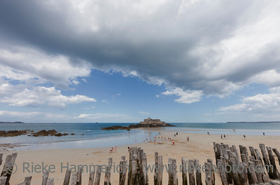 SAINT-MALO, FRANCE - JULY 6: People enjoying the beach in front of the tidal island Petit Be in Saint-Malo, France on July 6, 2011. The fort was built in the 17th century and designed by Vauban.