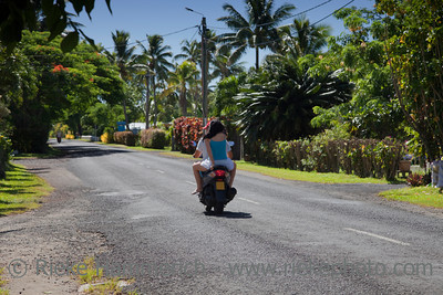 Couple Riding Motorbike - Rarotonga, Cook Islands, Polynesia, Oceania