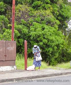 elderly woman rummaging in her bag - tobago, west indies