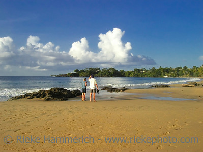 tropical beach with father and son - sunset on tobago, west indies