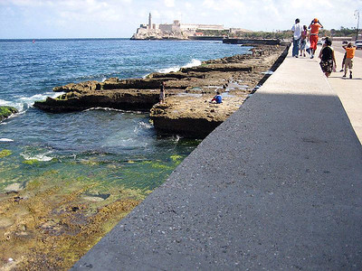 The 3-4 ft wide wall is El Malecon Havana, Cuba (as opposed to El Maricon which is something else). Here you can get a better perspective on the rocks (arrecifes?) below the wall. In the winter, the waves are big enough to wash over the malecon, all the way across the huge 4-lane Malecon Blvd.  The salt spray erodes the stucco cement facades of the buildings across the street in some areas of the boulevard.  Photo Credit Enrique Alfonso.
