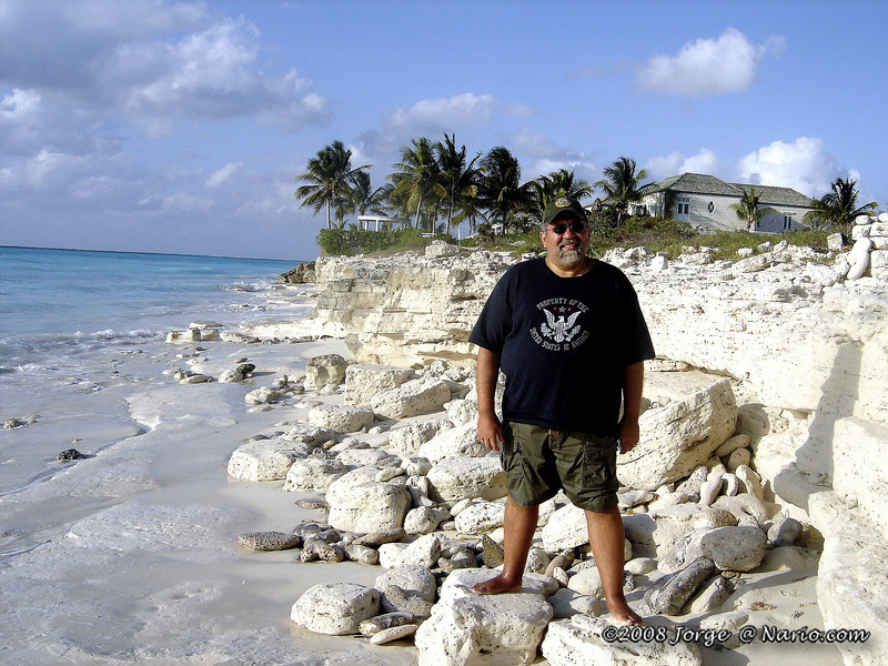 The house in the previous shot can be seen sideways in the background. You can see as you approach the house you run out of shoreline and have to climb the dark rocks... hence the previous photo. It wasn't always fun barefooted. [ Turks & Caicos ]