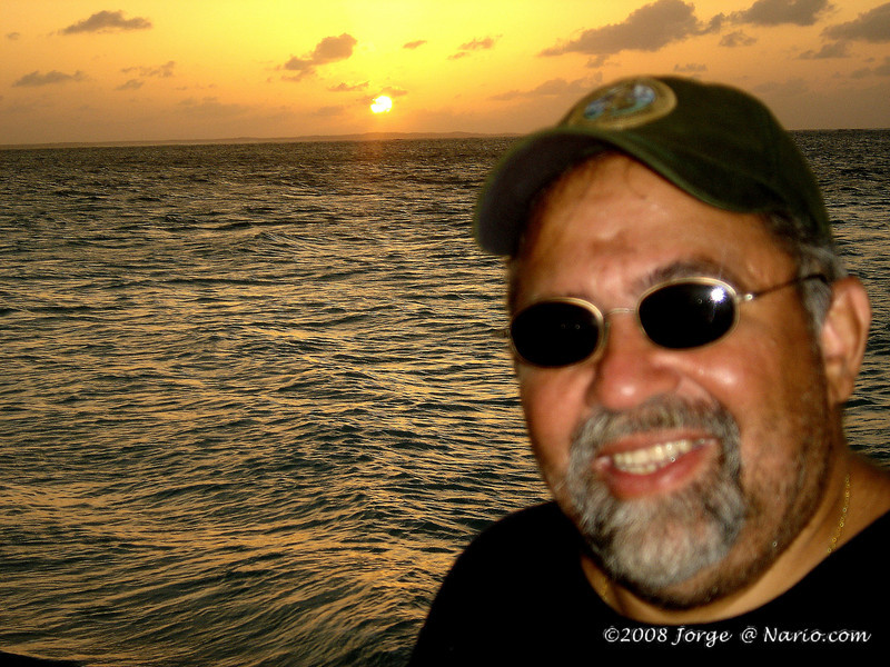 The photo looks fake but it is real (just poorly taken). My buddy loves to do this and this is is how he does it: he first gets an exposure for him (or in this case me) and then points to the setting sun. The camera didn't cooperate and refocused. Anyway ignoring my mug, it's a beautiful shot of the ocean and sun. [ Turks & Caicos ]