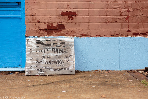 An old sign laying on a sidewalk
