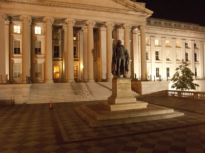 Treasury Department facade at night.