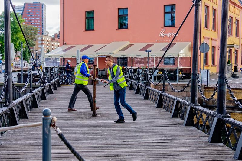 Manual drawbridge opened/closed by two men.