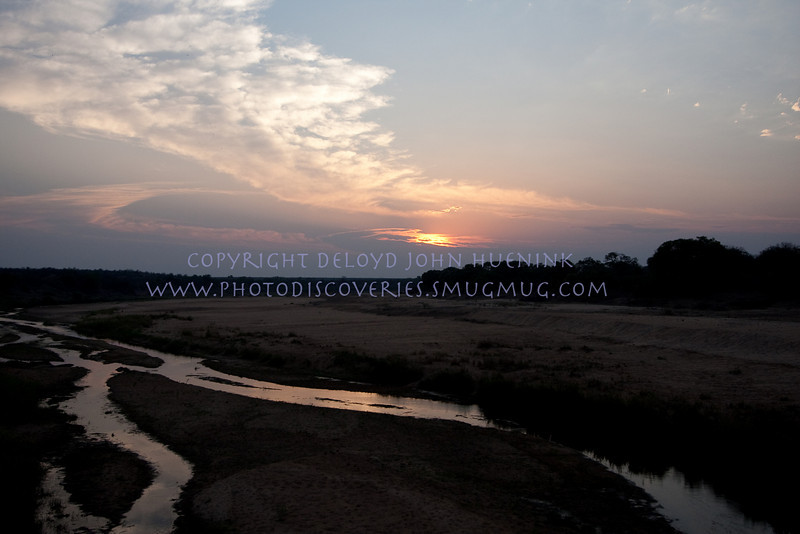 GLOWING<br /> <br /> Sunset on the African Plain.  The skies almost always provide a gift  at sunset.  Here the vivid colors reflect off the river.  This is the dry season, during the rainy season the river overflows the banks by the tree line on both sides.