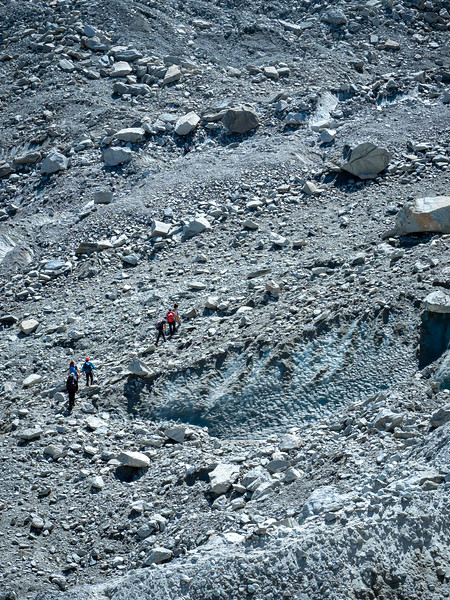 Hikers at the glacier. They are walking on glacier ice.