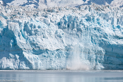 Hubbard Glacier at the head of Yukatat Bay, Alaska. The glacier is calving which is a sudden breaking away of a mass of ice. The calving is often preceded by a loud cracking or booming sound.