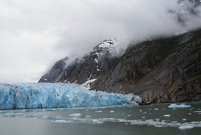 The foot of a glacier.  The walls are about 100 feet high.  Look to the right and find the boat.  The boat is about 35 feet long.