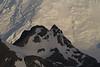 Imagen contraria a la anterior en la que un peñasco iluminado tenuemente por la luz difusa filtrada por las nubes interrumpe el impresionante telón de fondo de nieves perpetuas de una gran montaña iluminada en la Isla Livingston